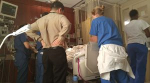 Wife at the hospital surrounded by doctors.