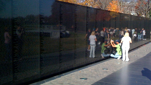 Man doing a pencil rubbing on the Vietnam War Memorial